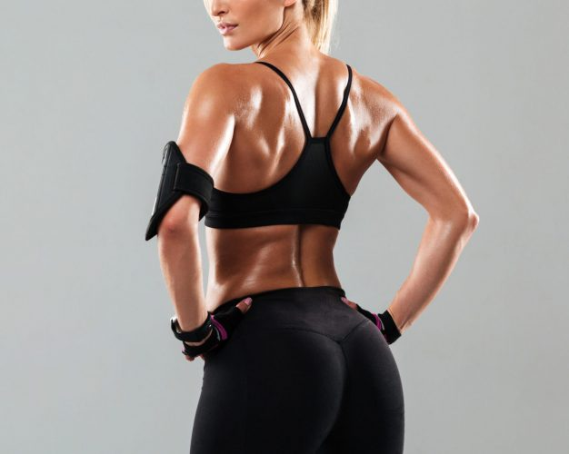 Back view portrait of a healthy muscular sportswoman standing isolated over gray background