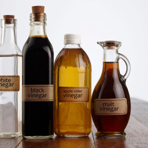 close-up-of-various-vinegars-on-table-against-white-background-963037322-c3194822685c4764980382ad5ed0edc3