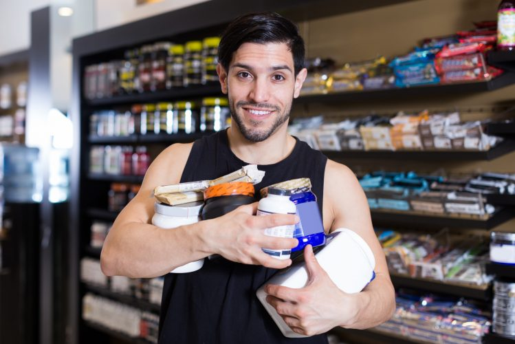 Smiling young sportman  keeping stack of sport nutrition products in sport shop