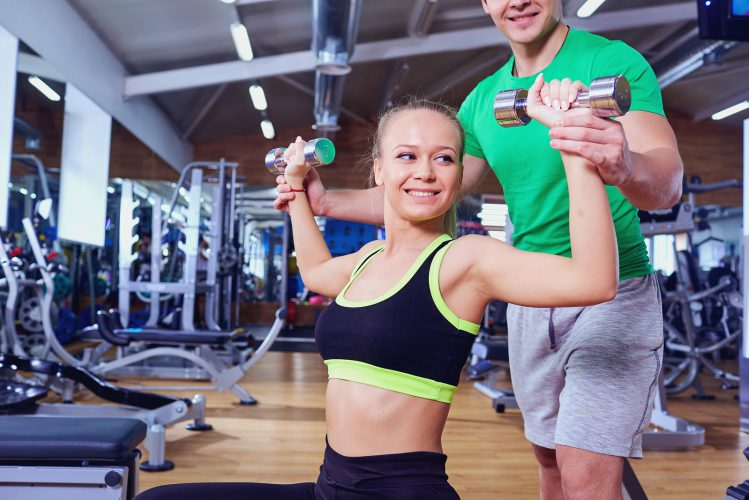 Personal trainer and girl with dumbbells doing exercises in the gym.