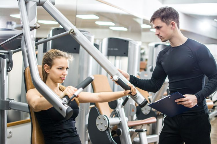 Sporty girl training on exercise machine with support of her personal trainer in gym