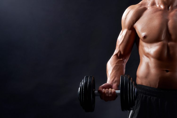 True hard worker. Cropped closeup of a strong muscular male holding a dumbbell posing against black background